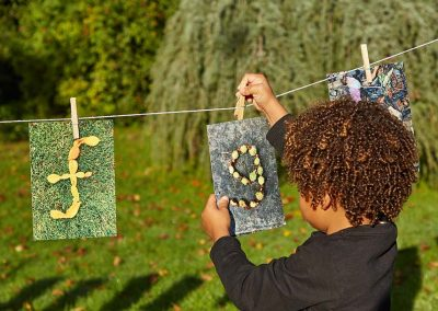 child hanging photos on washing line