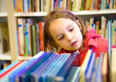 Young child browsing books in a library