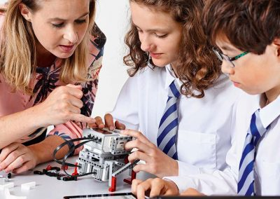 Three children learning to code with teacher